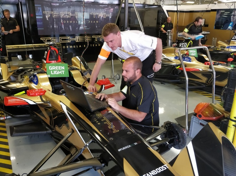 A Track Support Engineer assists with car setup before a Formula E race